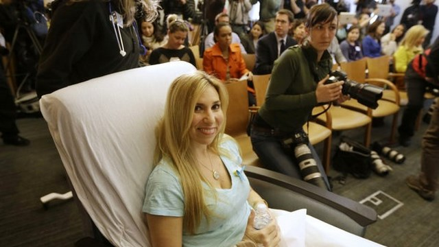 Heather Abbott, of Newport, R.I., is wheeled into a news conference past members of the media, behind, at Brigham and Women's Hospital, in Boston, Thursday, April 25, 2013. Abbott underwent a below the knee amputation during surgery on her left leg following injuries she sustained at the Boston Marathon bombings on April 15. (AP Photo/Steven Senne)