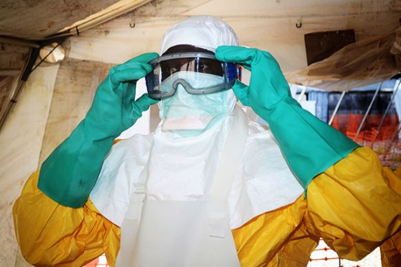 A member of Doctors Without Borders dons protective gear at the isolation ward of the Donka Hospital in Conakry, Guinea, where people infected with the Ebola virus are being treated. (Photo: Cello Binani/AFP/Getty Images)